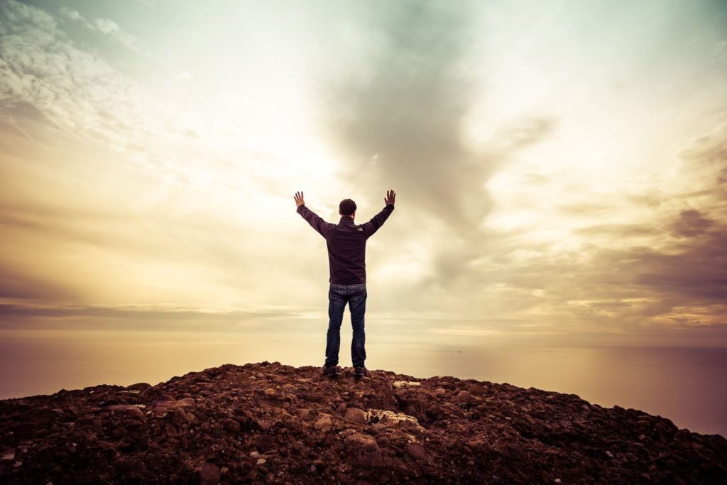 Mann streckt Hände gegen Himmel